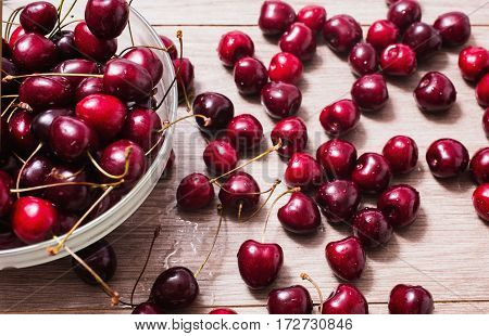 Ripe juicy red cherry with drops of water in a transparent plate on a wooden background. Cherries on the table
