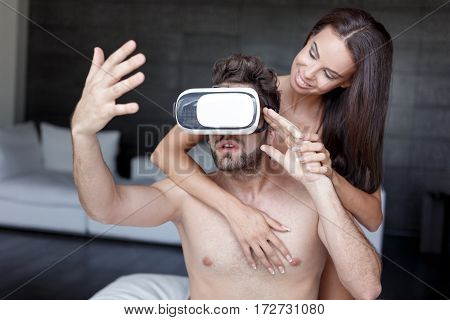 Young man playing virtual reality with headset and girlfriend indoor