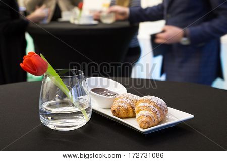 Two Plain Croissants With Chocolate Sauce On White Plate. With People In Background.