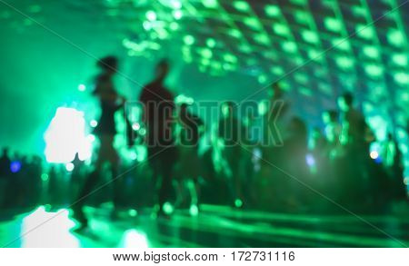 Abstract blurred people moving on and dancing at music night festival event - Defocused image of disco club party with laser show - Nightlife entertainment concept - Vivid greenery filter