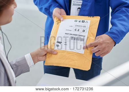 Delivery man showing business woman where she should write shipping address