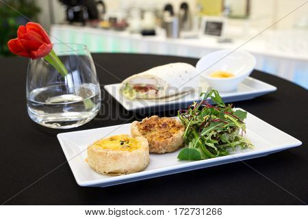 Two Quiches And Chicken Tortilla Wrap With Dip On Modern Plates.
