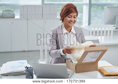 Business lady receiving parcel with sweater at work