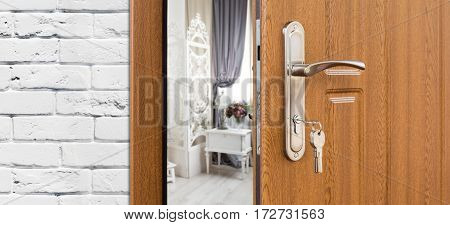 Half opened door to a shabby chic lounge room, handle closeup. Welcome, privacy concept. Entrance to the hotel suit, modern interior design.