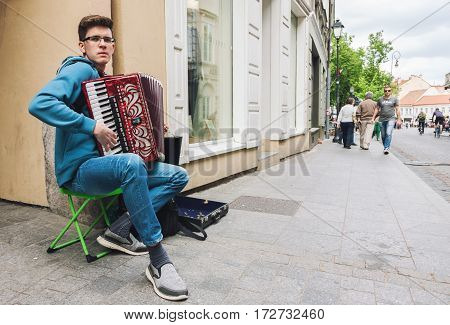 VILNIUS LITHUANIA - MAY 21 2016: Young accordionist performing solo on the street of Vilnius old town Lithuania