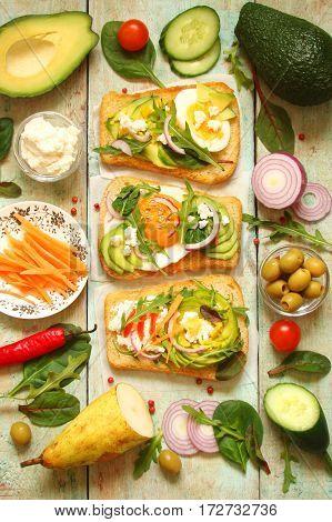 vegetarian sandwich with avocado cream cheese cucumber herbs carrot onion tomato