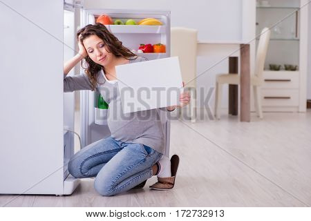 Pregnant woman near fridge with blank message