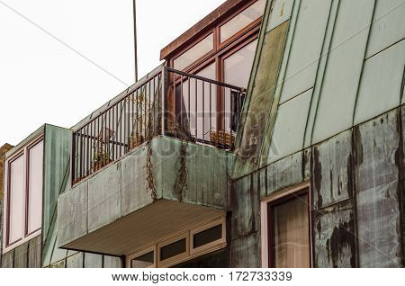 interesting balcony on the top of the building the whole building covered with copper red balcony window frames original architecture