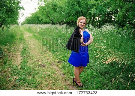 Young Overweight Girl At Blue Dress Posed Background Spring Garden.