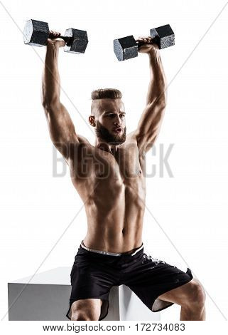 Muscular man working out with dumbbells. Photo of man isolated on white background. Strength and motivation.