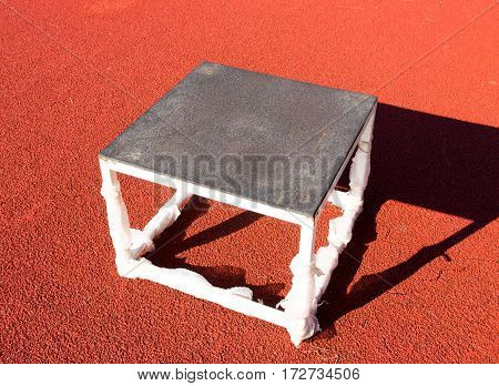 Plyo box sitting in track surface in the high jump area