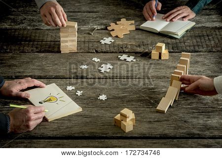 Businessmen sharing ideas concept. Close-up full frame image with hands of four people over rough wooden table with dominoes effect drawing light bulb puzzle pieces and other conceptual stuff.