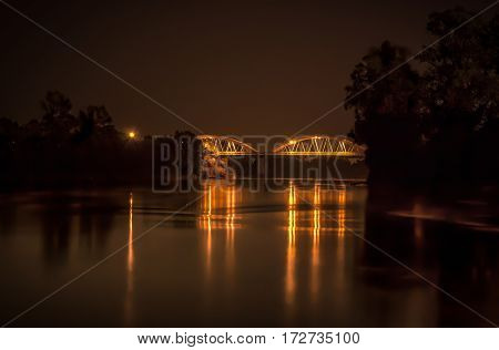 an illuminated bridge reflected in the river ... a unique emotion