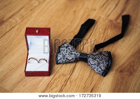 Wedding rings on red box belt and bow tie lie on the wooden background.