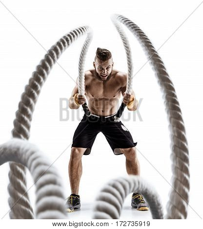 Attractive muscular man working out with heavy ropes. Photo of handsome man in sportswear isolated on white background