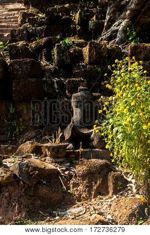 Wat Phu in Southern Laos - The path up the mountain, statue with fresh offerings and incense