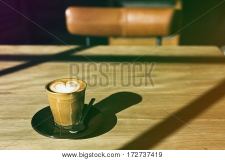 Coffee cup on the wooden table with gradient photo style