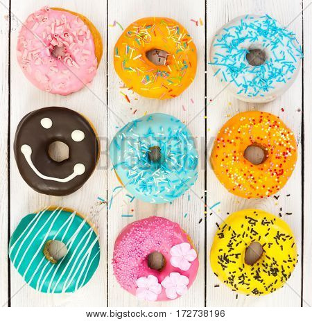 Different Colorful Donuts On Wooden Background
