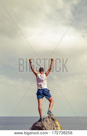 Success achievement running or hiking accomplishment business concept with man celebrating with arms up raised outstretched trekking climbing trail running outdoors