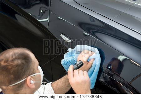 Man on a car wash polishing car with a polish machine