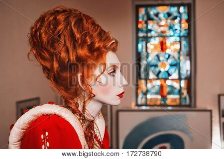 Redhead fashion model with blue eyes in red dress. Queen with a high hairdo. Vintage image. Model with pale skin. Updo in style fashion