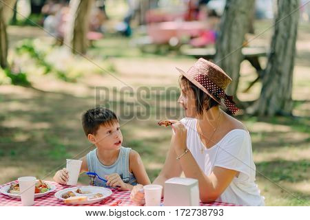 summer sunny day in nature at the table Mother and son eating