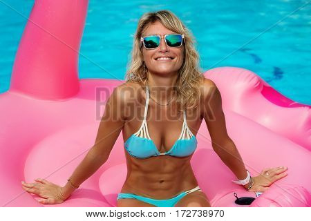 Young woman in the pool sitting on mattress