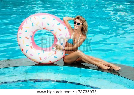 Young beautiful woman is relaxing in swimming pool with rubber ring.