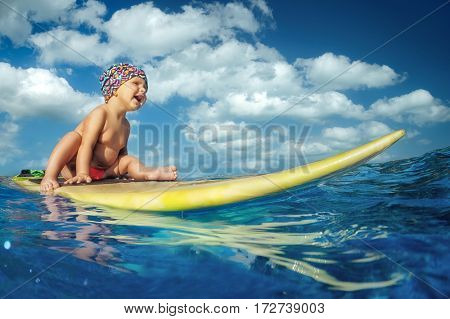 Baby Surfer sitting on surf board with fun on ocean waves