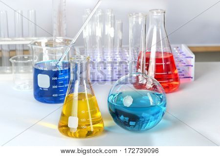 Laboratory glassware with solutions of different colors on white table