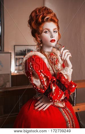 Redhead woman with blue eyes in red dress. Queen with a high hairdo. Vintage image. A woman with pale skin. Redhead model. Queen in red vintage dress. Beautiful fashion model