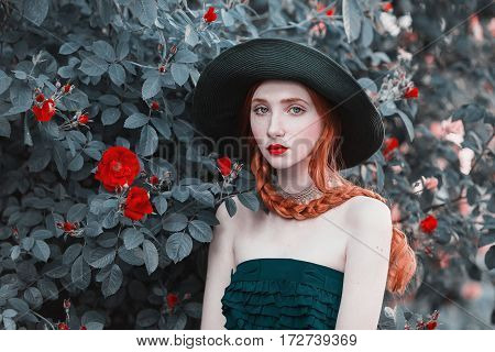 Redhead woman with blue eyes and pale skin in a green hat and dress with a red belt. Woman with long red hair against the backdrop of bush peach roses. Redhead model with red lips. Beautiful woman portrait on rose background
