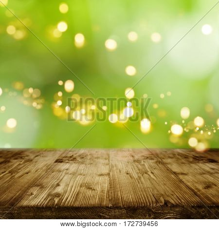 Fresh green spring background with sun and bokeh in front of a rustic wooden table for a concept