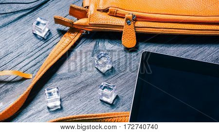 Summer fashion set with orange handbag and ice cubes