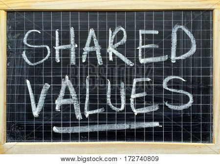 The words Shared Values written by hand in white chalk on a blackboard as a reminder to adopt the core values of your business