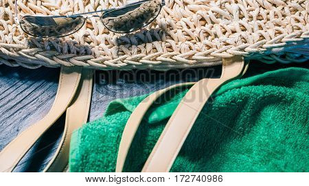 Summer fashion set with straw handbag, sunglasses and green towel