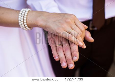 Groom and bride in white wedding dress on background of the arch. Wedding ceremony. Happy family with gold rings.