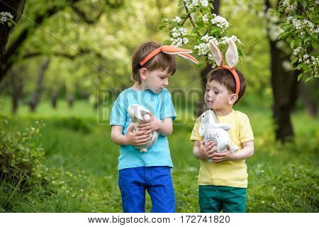 Two Little Kids Boys And Friends In Easter Bunny Ears During Traditional Egg Hunt In Spring Garden,