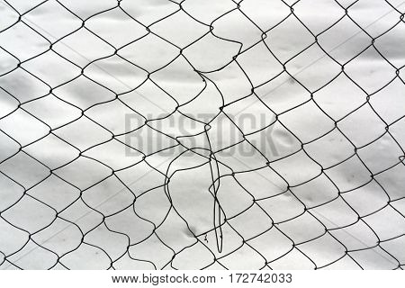 Damaged Mesh Wire Fence Against Snow.
