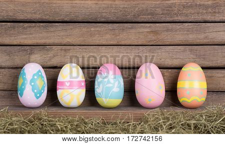 Colorful Easter eggs against a wood background