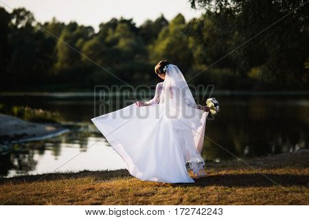 The bride in a white wedding gown on nature background. Wedding photography. White gown on woman