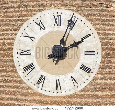 Old Cathedral clock on brick wall Bassano Italy
