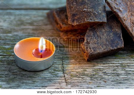 broken natural handmade chocolate in light of lit candle