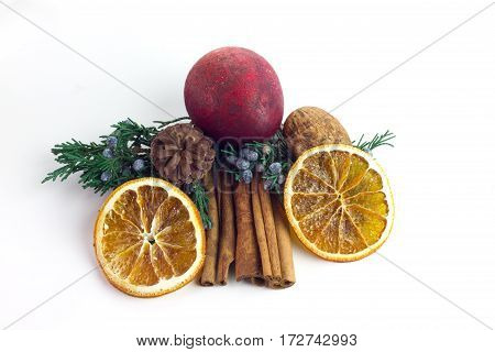 Cinnamon Sticks surrounded by potpourri orange slices pine branches berries and nuts isolated on a white background
