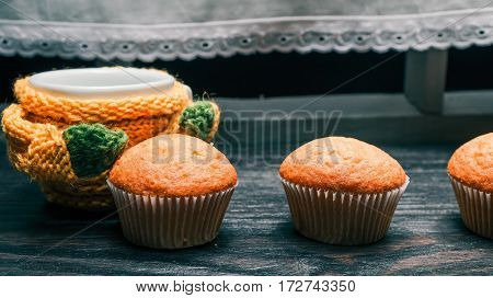 Tea cup in yellow sweater and small muffins in line