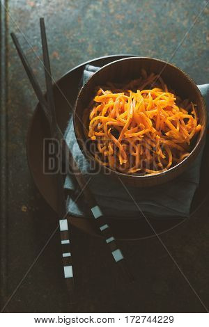 Carrots in Korean and spices in a bowl on wooden boards vertical