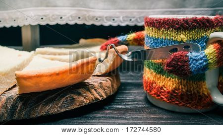 Mug in striped sweater holding teaspoon to take a piece of homemade cheesecake