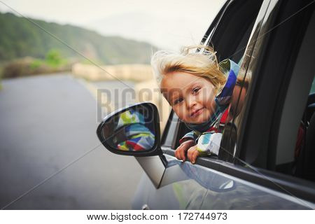 family travel - happy little girl travel by car on road