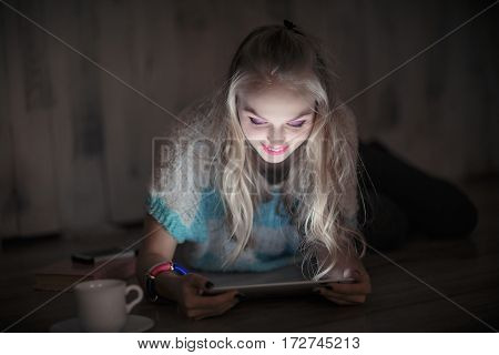 portrait of beautiful young blonde woman looks and reads on a tablet and drinking coffee at night. girl uses the tablet