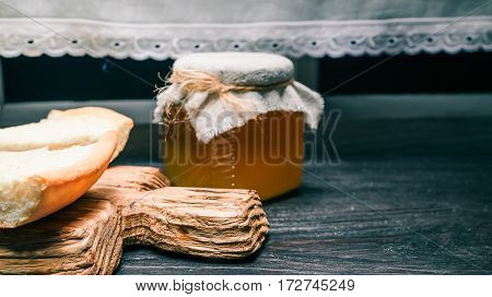 Homemade cheesecake pieces on wooden serving board and honey jar